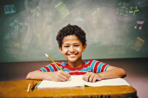 Boy writing and smiling