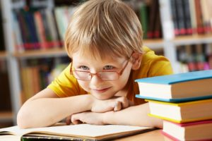 Boy leaning on books smiling