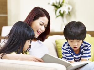 Image of a mother reading with her daughter and son.