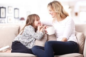 Image of a mother and daughter sitting together on couch and talking.